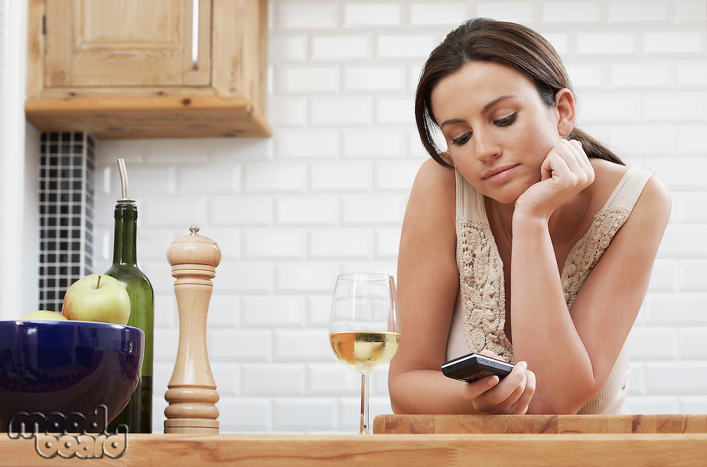 Young woman text messaging leaning on kitchen counter