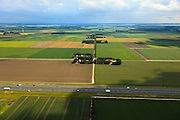 Nederland, Noordoostpolder, 30-06-2011; Johannes Postweg (doorsneden door de A6), Nagele rechts aan de horizon. De Noordoostpolder (NOP), is een voorbeeld van moderne grootschalige polder met rationele verkaveling. De aanleg van de polder maakte  deel uit van de Zuiderzeewerken (plan Lely) en viel in 1942 droog. De meeste boerderijen (en dorpen) zijn van na de tweede wereldoorlog..The northeast polder (NOP), is an example of modern large-scale polder with rational allotment. The construction of the polder was part of the Zuiderzee Works (Lely plan), in 1942 the polder was dry. Most of the building, farmhouses and villages, is post-war..luchtfoto (toeslag), aerial photo (additional fee required).copyright foto/photo Siebe Swart