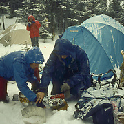 Man and woman light a stove on a winter camping trip in the White Mountain National Forest