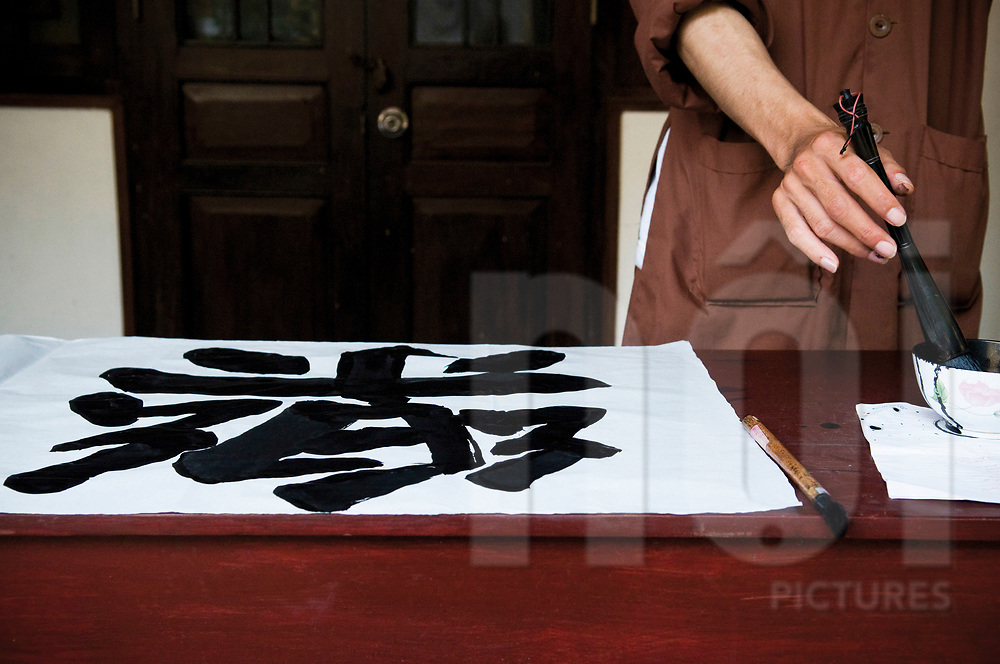 Monk practices chinese calligraphy in a temple of Hanoi, Vietnam, Southeast Asia