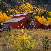 A red barn is embraced by aspens in their fall finery near Twin Lakes, Colorado