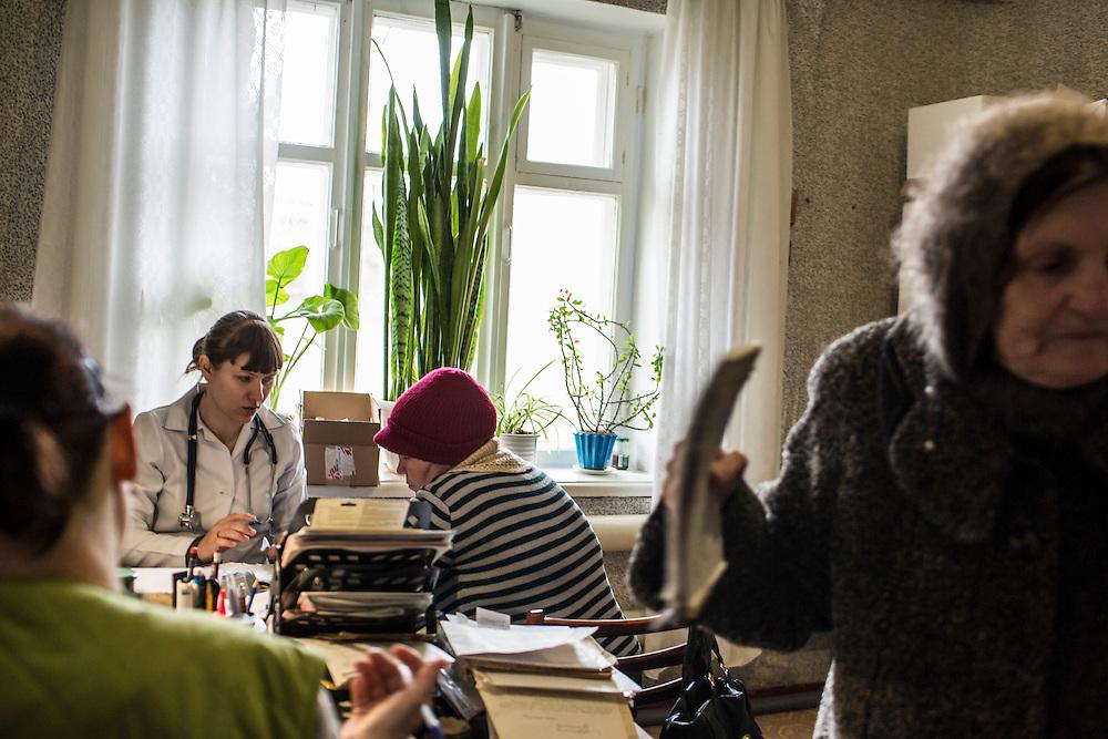 ZIMOGORYE, UKRAINE - MARCH 15, 2015: Yelena Beybudova, left, a nurse, and Yevgeniya Kovalenko, a general practitioner, second from left, consult with patients at the Zimogoryivskaya Ambulatory in Zimogorye, Ukraine. CREDIT: Brendan Hoffman for The New York Times