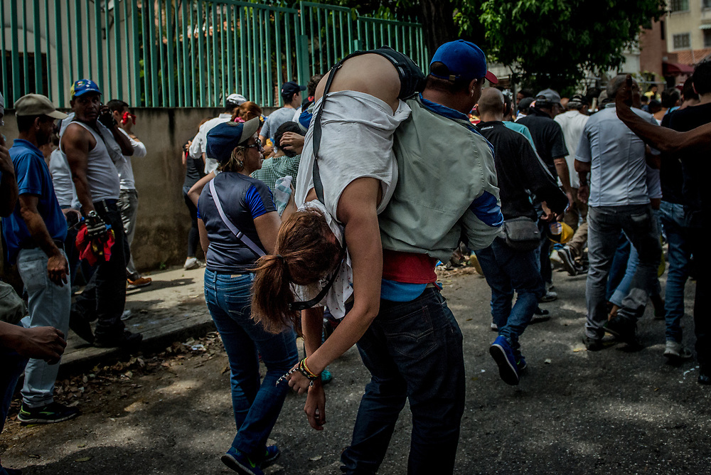 CARACAS, VENEZUELA - APRIL 19, 2017:  Opposition protesters take an injured woman to safety. Thousands of protesters took to the streets today in Venezuela to show their discontent with the government.  They were met by riot police that fired tear gas and rubber bullets at them.  Some protesters responded by throwing rocks and petrol bombs.  Venezuela is in crisis, and residents face daily struggles over food and medicine shortages, and one of the highest crime rates in the world.  PHOTO: Meridith Kohut