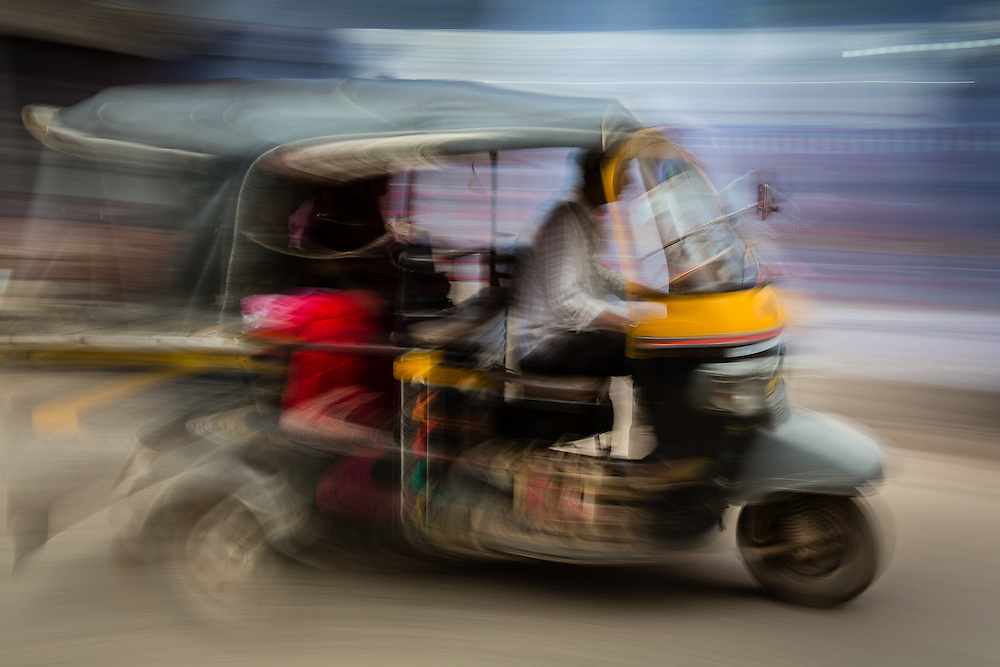 A panning shot of a passing rickshaw