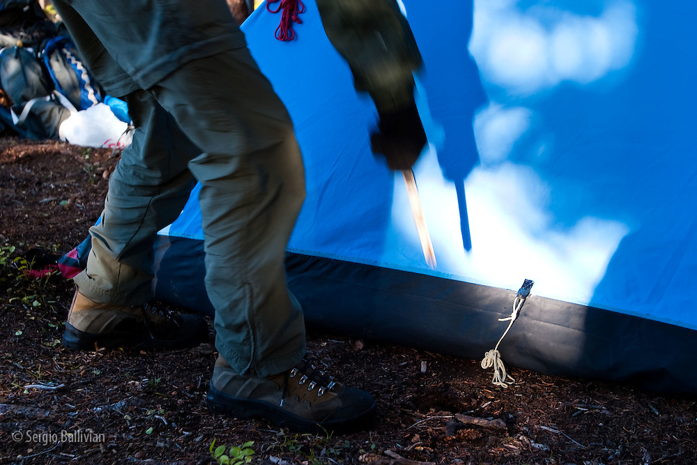A person pulls a tent stake out of the ground before packing up in Colorado.