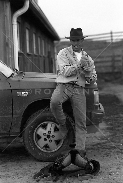 rugged man leaning on a truck on a ranch