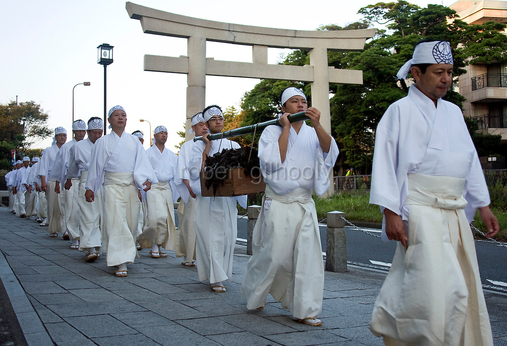 A box filled with seaweed past a torii gate in the middle of the main street by priests during a purification ritual known as hamaorisai at the start of the 3-day Reitaisai festival in Kamakura, Japan on  14 Sept. 2012.  As a symbol of the purification, priests collect the seaweed from the sea and take it back to the shrine, hanging pieces around the shrine grounds to appease the gods. Photographer: Robert Gilhooly.