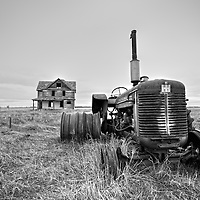 Derelict farm machinery with house in Pierce County USA