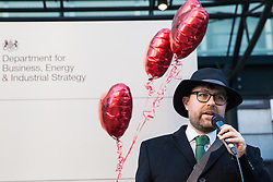 London, UK. 14th February, 2019. A member of Poetry on the Picket Line performs for outsourced support staff from the Public & Commercial Services (PCS) union on a Valentine's Day-themed picket line outside the Department of Business, Energy and Industrial Strategy (BEIS) during strike action to demand the London Living Wage and an end to outsourcing.