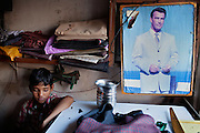 A boy is sitting inside his father's small tailor shop near Oriya Basti, one of the water-affected colonies of Bhopal, Madhya Pradesh, India, near the abandoned Union Carbide (now DOW Chemical) industrial complex, site of the infamous 1984 gas tragedy. The poisonous cloud that enveloped Bhopal left everlasting consequences that today continue to consume people's lives.