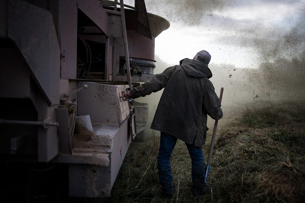 Marty Vig cleans out a jam in the hay grinder while working on bales south of Meadow, SD on October 4, 2017. One of Vig's few sources of income after spending 20 years in prison for manslaughter, he bought the rig from his son who was having trouble making payments himself because of the harsh realities of the economy of rural life.