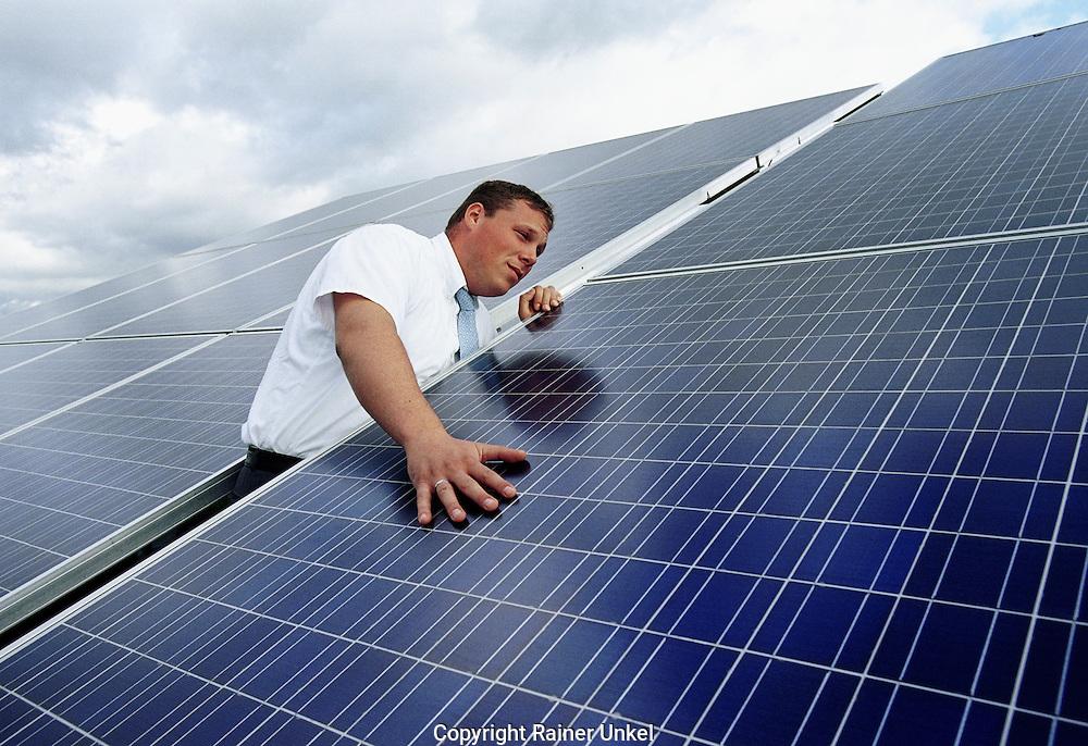 DEUTSCHLAND : Ein Mitarbeiter der Pfalzwerke AG ueberprueft die Solarpanels / Sonnensegel einer grossen Photovoltaik-Anlage in Neustadt / Strom / Stromerzeugung / Photovoltaik. GERMANY : An employee of Pfalzwerke AG is checking the solar panels of a huge photovoltaic unit in Neustadt / Power Generation . 20.08.2004.  Foto : Copyright by Rainer UNKEL.          Tel.: (0)228 / 477211 , Fax: (0)228 / 477212
