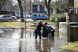 © Licensed to London News Pictures. 22/02/2014. Basingstoke, Hampshire. A man pushing a woman in a wheelchair through floodwater on Grampian Way in the Buckskin area of Basingstoke, Hampshire. Groundwater levels are continuing to rise in the area, forcing 69 homes to be evacuated in the Buckskin Area of the commuter town. Photo credit : Rob Arnold/LNP