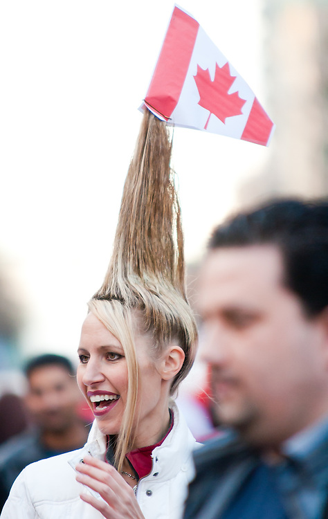 A woman with spiked blonde hair and doning a Canadian flag displays her creation to the crowds in Downtown Vancouver.<br /> <br /> Tens of thousands of people in Vancouver took to the streets on Sunday 28th February 2010 to celebrate Canada's 3-2 overtime win over the United States for the gold medal in men's Olympic hockey...Traffic came to a halt in and around the downtown of the host city for the Winter Games following the dramatic finish to the match, which featured Sidney Crosby scoring to secure the victory on the final day of Olympic competition.