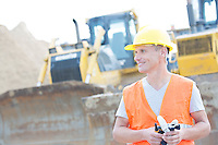 Smiling supervisor looking away at construction site