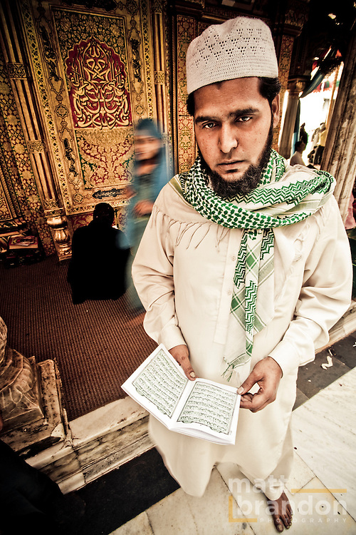 A man stands in front of the Nizamuddin Darga or tomb and reads the Koran that is provided by the people that run the shrine.