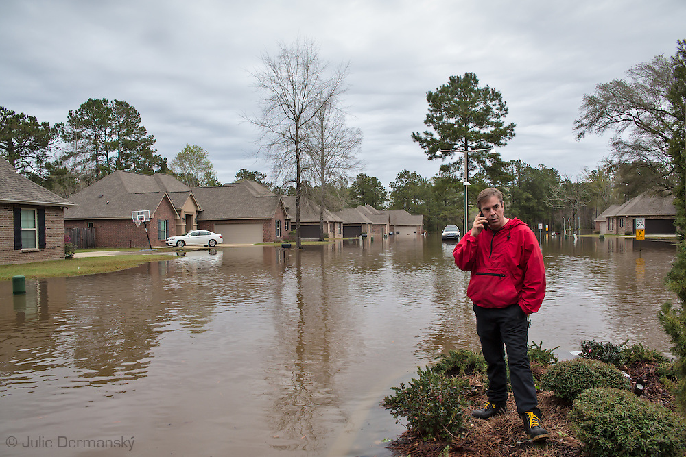 Covington Louisiana, March, 12, 2016, Man making a call trying to locate his son who is visiting another child in the flooded Tallow Creek subdivision behind him. 14 inches of rain fell in less than 24 hours, after three days of intermittent rain, causing flash floods. The Tchefuncte River  and Bogue Falaya River<br />  crested on Saturday morning but the flood event continued into the night for those in Tallow Creek.
