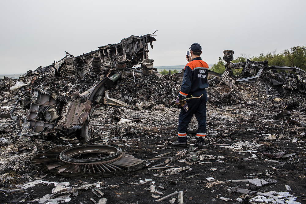 GRABOVO, UKRAINE - JULY 18: An emergency services worker photographs debris from an Air Malaysia plane crash on July 18, 2014 in Grabovo, Ukraine. Malaysia Airlines flight MH17 travelling from Amsterdam to Kuala Lumpur has crashed on the Ukraine/Russia border near the town of Shaktersk. The Boeing 777 was carrying 280 passengers and 15 crew members. (Photo by Brendan Hoffman/Getty Images) *** Local Caption ***