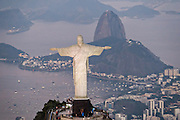Christ the Redeemer statue on Corcovado Mountain looking toward Sugarloaf and Guanabara Bay at sunset in Rio de Janeiro, Brazil.