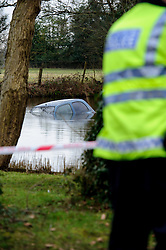© Licensed to London News Pictures. 21/02/2013 London, UK. A car submerged in a lake in Totteridge, NW London after a 32 year old woman drove the Nissan Micra into the freezing water. Two Met Police constables swam out to rescue the unconscious driver, smashing the  car windows with a hammer..Photo credit : Simon Jacobs/LNP