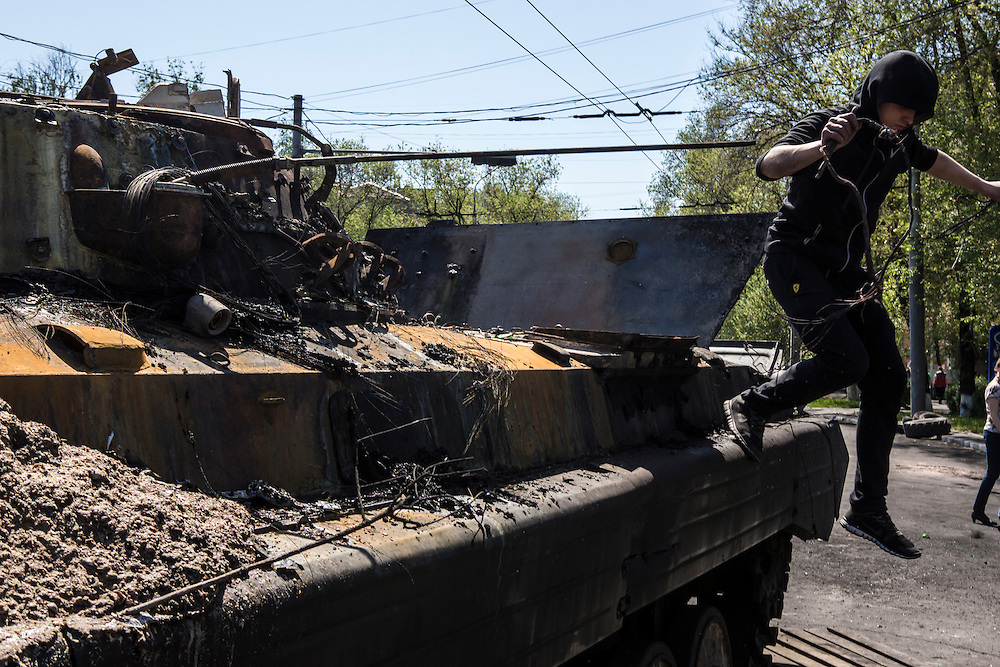 MARIUPOL, UKRAINE - MAY 10: A man takes wires from a burned tank a day after deadly clashes on May 10, 2014 in Mariupol, Ukraine. A referendum on greater autonomy is planned for the region tomorrow. (Photo by Brendan Hoffman/Getty Images) *** Local Caption ***