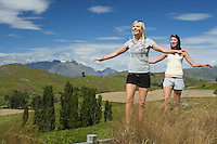 Women balancing on fence in field with mountains behind