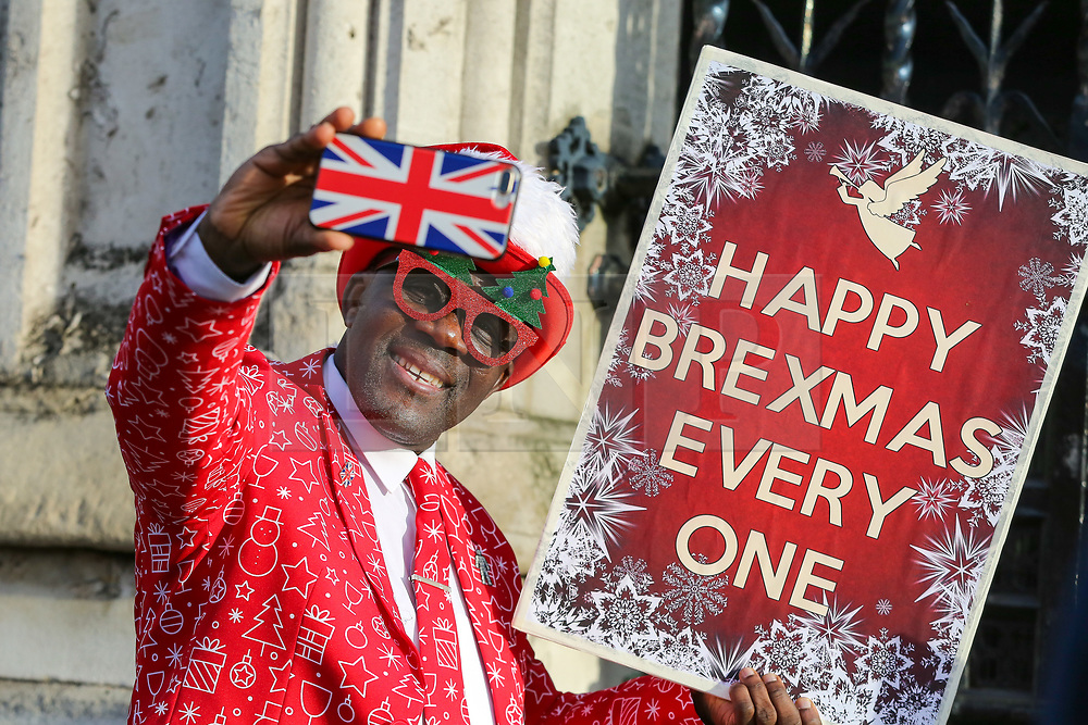 © Licensed to London News Pictures. 18/12/2019. London, UK. A Pro-Brexit supporter takes a selfie while holding a 'HAPPY BREXMAS EVERYONE' placard outside the Houses of Parliament. Photo credit: Dinendra Haria/LNP