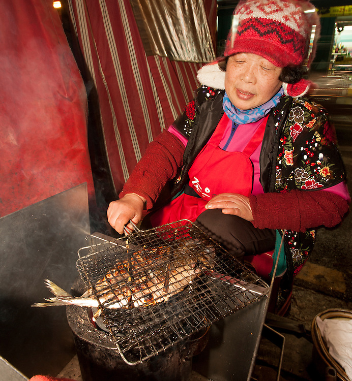 A pojangmacha proprietor grills fish outside her food tent in Seomyeon. Busan, South Korea.