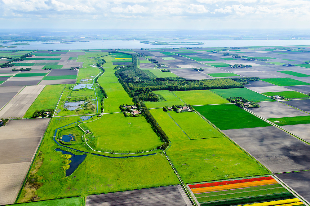 Nederland, Flevoland, Noordoostpolder, 07-05-2015; Schokland, noordelijk punt van het voormalig eiland in de Zuiderzee, met restanten van de voormalige haven Emmeloord, vuurtoren, lichtwachterswoning.<br /> Onderdeel van de UNESCO Werelderfgoedlijst. Het verlagen van de grondwaterspiegel in de Noordoostpolder leidt tot inklinking waardoor het eiland steeds lager komt te liggen. Om verder wegzinken te voorkomen een hydrologische zone aangelegd.<br /> Village and former island. Part of the UNESCO World Heritage List. The center is the Reformed Church. Lowering the groundwater level in the Noordoostpolder leads to subsidence and causes the island the sink away. In order to prevent further decline a hydrological zone has been created.<br /> luchtfoto (toeslag op standard tarieven);<br /> aerial photo (additional fee required);<br /> copyright foto/photo Siebe Swart