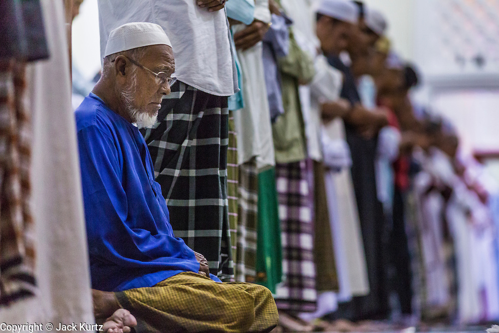 11 JULY 2013 - PATTANI, PATTANI, THAILAND:  Men pray in the Pattani Central Mosque in Pattani, Thailand, Thursday night during Ramadan services. The mosque is one of the busiest in south Thailand. About 15,000 people attend nightly Ramadan services in the mosque. Ramadan is the ninth month of the Islamic calendar, and the month in which Muslims believe the Quran was revealed. Muslims believe that the Quran was sent down during this month, thus being prepared for gradual revelation by Jibraeel (Gabriel) to the Prophet Muhammad. The month is spent by Muslims fasting during the daylight hours from dawn to sunset. Fasting during the month of Ramadan is one of the Five Pillars of Islam.     PHOTO BY JACK KURTZ