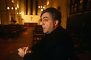 Father Peter Geldard sits in his former Anglican Church near Faversham, England. He sits in a pew clasping his hands together and looking away as if lost in thought, the Christian cross and altar in the distance. Geldard is known for his stance against the Church of England's vote allowing the ordination of women priests in 1992, causing a huge row with Anglican church worshippers. Clergy, including five bishops, eventually left to join the Catholic Church including Father Geldard, who led the opposition and became a notorious debater, campaigner, and general nuisance to the church. He eventually resigned from his Anglican orders, moved out of his vicarage house and along with thirty-five members of his former parish (including the churchwardens and all the members of the parish council), now attends Mass at the Catholic church in Faversham. .