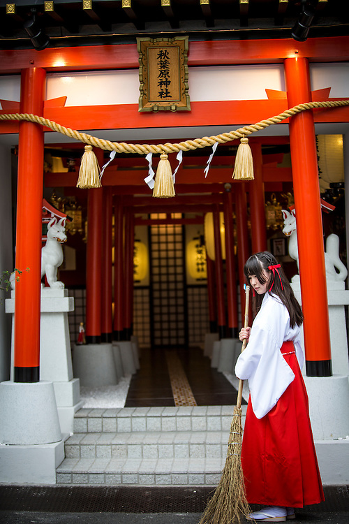 """TOKYO, JAPAN - JUNE 27 : A shrine maiden posed for a portrait in front of the entrance of Akihabara shrine in Akihabara, Tokyo, Japan on June 27, 2016.  A newly opened Akihabara Shrine offers a memorial services for """"deceased"""" anime figures. Photo by Richard Atrero de Guzman"""
