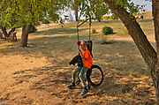 Boy on swing in recreation area<br />Grasslands National Park<br />Saskatchewan<br />Canada