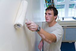 Bulgarian painter and decorator using paint roller on wall,