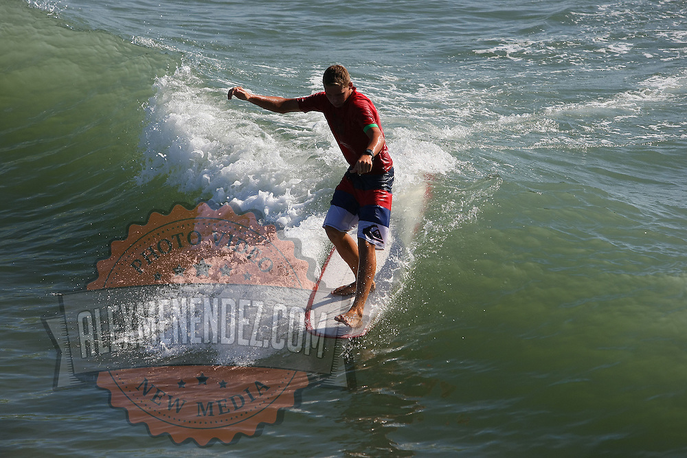 A competitive long boarder rides a wave during the 28th annual National Kidney Foundation, Rich Salick Pro/Am surf festival takes place at the the Cocoa Beach pier on Saturday,  September 2, 2013 in Cocoa Beach, Florida. This event raises thousands of dollars for people with kidney disease and also benefits the services of the NKF of Florida. (AP Photo/Alex Menendez)