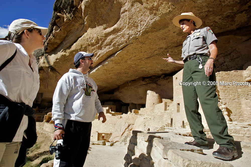 Mesa Verde National Park Ranger Tammi Corchero (far right) talks with Heather Ficke (far left) and Vince Toms (center) during an hour long tour of the Cliff Palace site at Mesa Verde National Park one afternoon. Ficke and Toms are from Crestline, Ca. and said it was their first time at Mesa Verde. The cliff dwellings at Cliff Palace were discovered in 1888 by cowboys Richard Wetherill and Charlie Mason. The archeological sites found in Mesa Verde National Park, near Cortez, Co., are some of the most notable and best preserved sites in the United States. Mesa Verde offers visitors a spectacular look into the lives of the Ancestral Pueblo people. The culture represented at Mesa Verde reflects more than 700 years of history. From approximately A.D. 600 through A.D. 1300 people lived and flourished in communities throughout the area, eventually building elaborate cliff dwellings in the sheltered alcoves of the canyon walls. Mesa Verde National Park is a U.S. National Park and UNESCO World Heritage Site located in Montezuma County, Colorado, United States. The park occupies 81.4 square miles (211 square kilometers) and features numerous ruins of homes and villages built by the ancient Pueblo people. It is best known for several spectacular cliff dwellings ? structures built within caves and under outcroppings in cliffs ? including Cliff Palace, which is thought to be the largest cliff dwelling in North America..(MARC PISCOTTY/ © 2005)