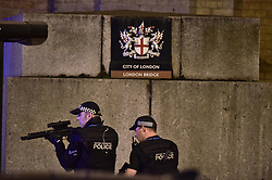 """Armed Police officer looks through his weapon on London Bridge as police are dealing with a """"major incident"""" at London Bridge."""