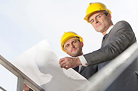 Low angle portrait of confident young businessmen holding blueprint against clear sky