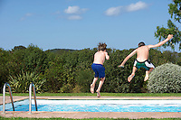 Two boys (6-11) jumping into pool back view