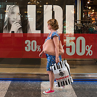 MILAN, ITALY - JULY 03:  A girl walks past a sale sign in the fashion district of Milan on July 3, 2010 in Milan, Italy. Milan's summer sales start today. .***Agreed Fee's Apply To All Image Use***.Marco Secchi /Xianpix. tel +44 (0) 207 1939846. e-mail ms@msecchi.com .www.marcosecchi.com