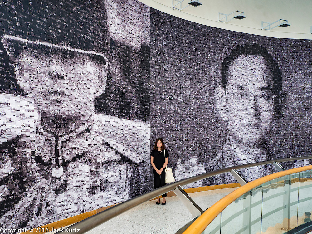"06 NOVEMBER 2016 - BANGKOK, THAILAND: A Thai woman stands in front of large mosaic photos of Bhumibol Adulyadej, the late King of Thailand at the Bangkok Art and Culture Centre. The Royal Photographic Society of Thailand with the Bangkok Art and Culture Centre and Thai Beverage Public Company Limited are hosting a photography exhibition to commemorate the late Thai King Bhumibol Adulyadej. The ""In Remembrance of His Majesty King Bhumibol Adulyadej"" Photography Exhibition is dsiplaying 89 photographs by 89 photographers honoring King Bhumibol Adulyadej's legacy. The King was an avid photographer was usually seen with a camera in his hands. The exhibition will be on display until 27 November 2016 on the Curved Walls on the 3rd - 5th floor, Bangkok Art and Culture Centre.     PHOTO BY JACK KURTZ"