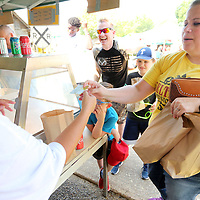 Jessica Watts, of Tupelo, pays for four Dudie Burger combos for her and her family during the 2019 Dudie Burger Festival Saturday at the Oren Dunn City Museum in Tupelo.