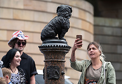 Tourists photograph statue of Greyfriars Bobby in old Town of Edinburgh, Scotland, UK