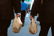 close up of two business men walking with lunch bags in there hands