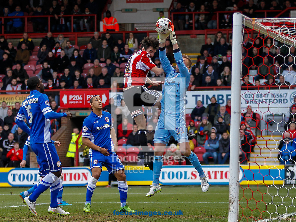 Jonathan Douglas of Brentford bundles former team mate Montell Moore of Brentford into the goal during the Sky Bet Championship match between Brentford and Cardiff City at Griffin Park, London<br /> Picture by Mark D Fuller/Focus Images Ltd +44 7774 216216<br /> 14/03/2015
