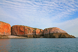 Stunning rock formations near The Sisters in Yampi Sound.  The distinctive tide line seen around the Kimberley coast is visible at low tide, as are small beaches that form after erosion causes clefts in the cliffs.