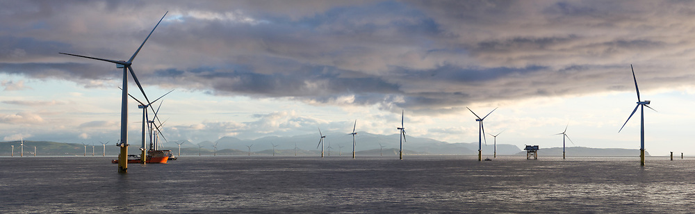 © Rob Arnold.  04/04/2014. North Wales, UK. An evening panoramic of the Gwynt y Môr Offshore Wind Farm off the coast of North Wales. The mountains of Snowdonia National Park can be seen in the distance. Photo credit : Rob Arnold
