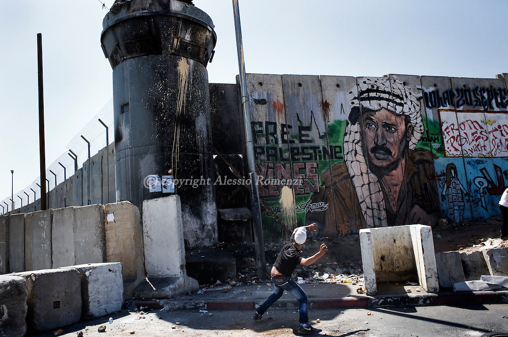 RAMALLAH : Palestinian stone throwers pelt rocks at an Israeli watch tower during a demonstration in front of the Qalandia check point on September 17, 2011, at the entrance of Jerusalem to support the Palestinian bid to the UN to become the 194th member state.ALESSIO ROMENZI