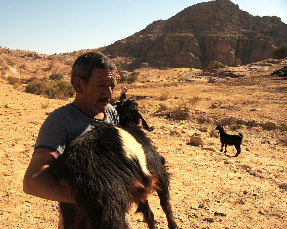 Suleiman carrying the goat he will kill to honor his guests with the traditional bedouin dish, 'mensef'
