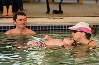 Patrick looks on as his son Henry floats with Instructor Martha McIntire during the Taylor Home's Water Babies/Grandbabies class on Saturday morning. (Karen Bobotas/for the Laconia Daily Sun)